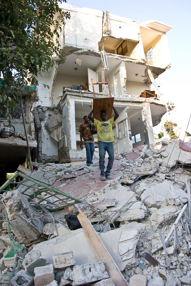 Homens tentam salvar móveis de uma casa arruinada pelo terremoto em Porto-Príncipe. Foto de Georgia Popplewell postada no Flickr sob uma licença Creative Commons.