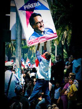 Homem tentando retirar o cartaz eleitoral de Piñera durante o enterro de Victor Jara que foi assassinado durante a ditadura de Pinochet. Foto tirada pelo usuário do Flickr Amable Odiable e usada sob licença da Creative Commons.