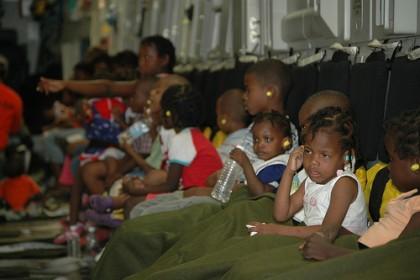 Crianças do orfanato Maison Des Enfants de Dieu na Base da Força Aérea Travis, Califórnia, C-17, 23 de janeiro, preparando-se para viajar para os Estados Unidos e encontrar suas famílias adotivas. Imagem do Flickr por DVIDSHUB. Usada sob uma licensa Creative Commons.