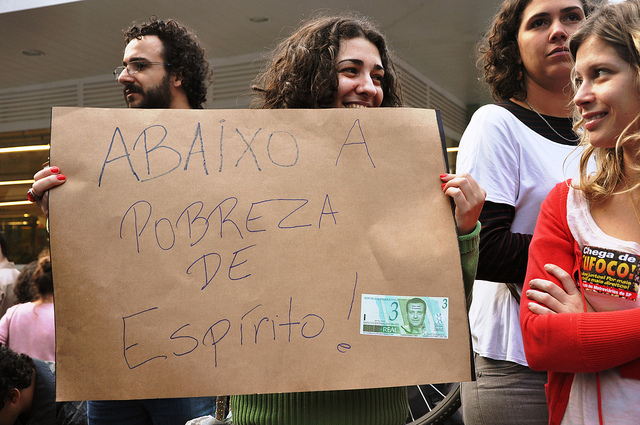 "A protester holds a post saying ""Down with the poverty of spirit!"". Photo by Fernando Baldan, on Flickr. Published with permission."