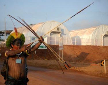 Indigenous wields bow and arrow in front of the construction site. © Ivan Canabrava/ Illuminati filmes shared by Xingu Vivo (used with permission)