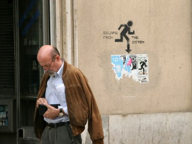 "Graffiti in a street of Lisbon ""Escape from the system"" - the caption reads ""Man looking for money for the ticket"". Photo by Trois Têtes (TT) on Flickr (CC BY-NC 2.0)"