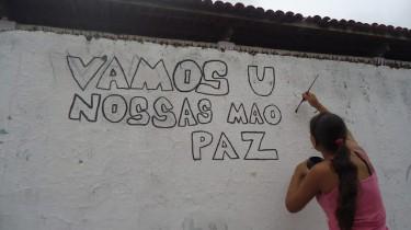 """Pintura de muro durante cortejo: """"Vamos unir nossas mãos pela paz"""". Foto publicada no blog Luthieria Cultural."""