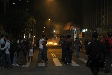 Um casal se abraça perto de uma das várias barricadas de lixo pegando fogo espalhadas pelo entorno da Avenida Paulista. Foto de Raphael Tsavkko Garcia, sob licença CC