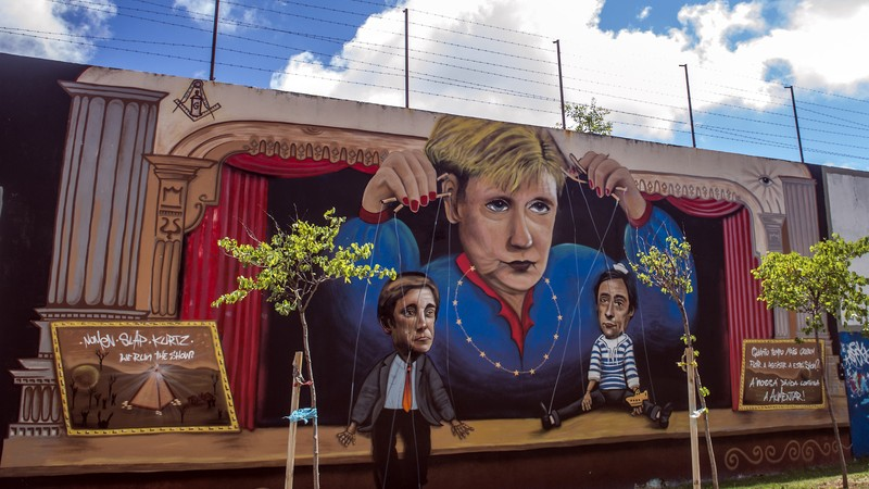 Graffiti with German chancellor Angela Merkel as a puppet master, holding the Portuguese Prime Minister and the Deputy Minister.