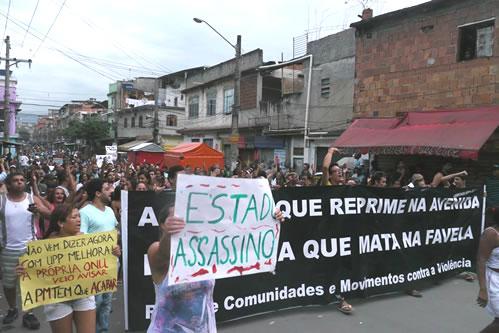 """Moradores da Maré protestam no dia seguinte à chacina, em 2013. Uma faixa diz: """"A polícia que reprime na avenida é a mesma que mata na favela"""". Foto por Equipe Marcelo Freixo (Flickr) CC BY 2.0"""