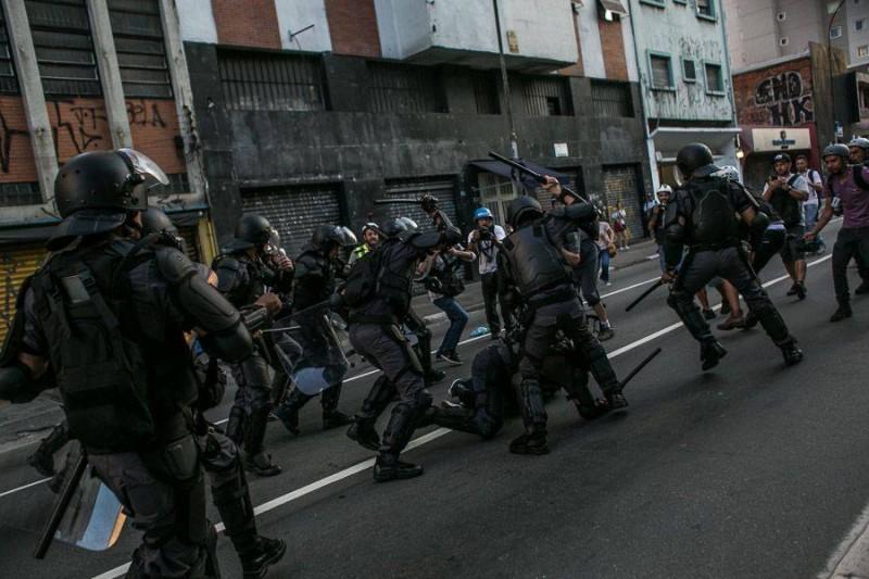 Manifestante no chao é agredido por meia dúzia de policiais. Foto de Mídia Ninja, uso livre.