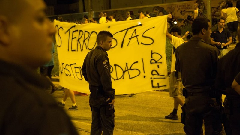 """Manifestantes carregam uma faixa com com os dizeres: """"os terroristas vestem fardas"""". Foto: Gulherme Fernández."""