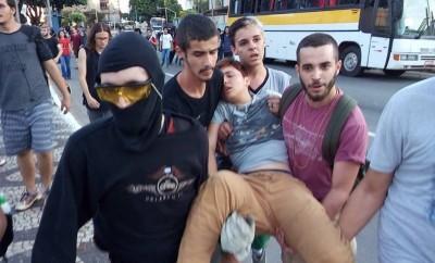 Estudante é carregado por colegas durante repressão em Goiás. Foto: Desneuralizador, uso livre