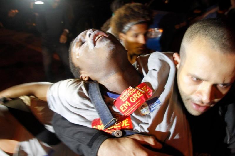 Estudante é carregado enquanto a Polícia Militar desocupa dcom violência a SEDUC do Rio. Foto via Desneuralizador