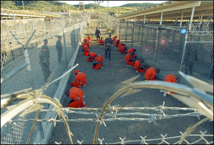 """Prisioneiros aguardam para serem """"processados"""" à chegada à prisão de Guantánamo em janeiro de 2002. Foto de Arquivo: Petty Officer 1st class Shane T. McCoy, U.S. Navy. - http://www.scoop.co.nz/stories/WO0201/S00047.htm, Public Domain, https://commons.wikimedia.org/w/index.php?curid=3936190"""