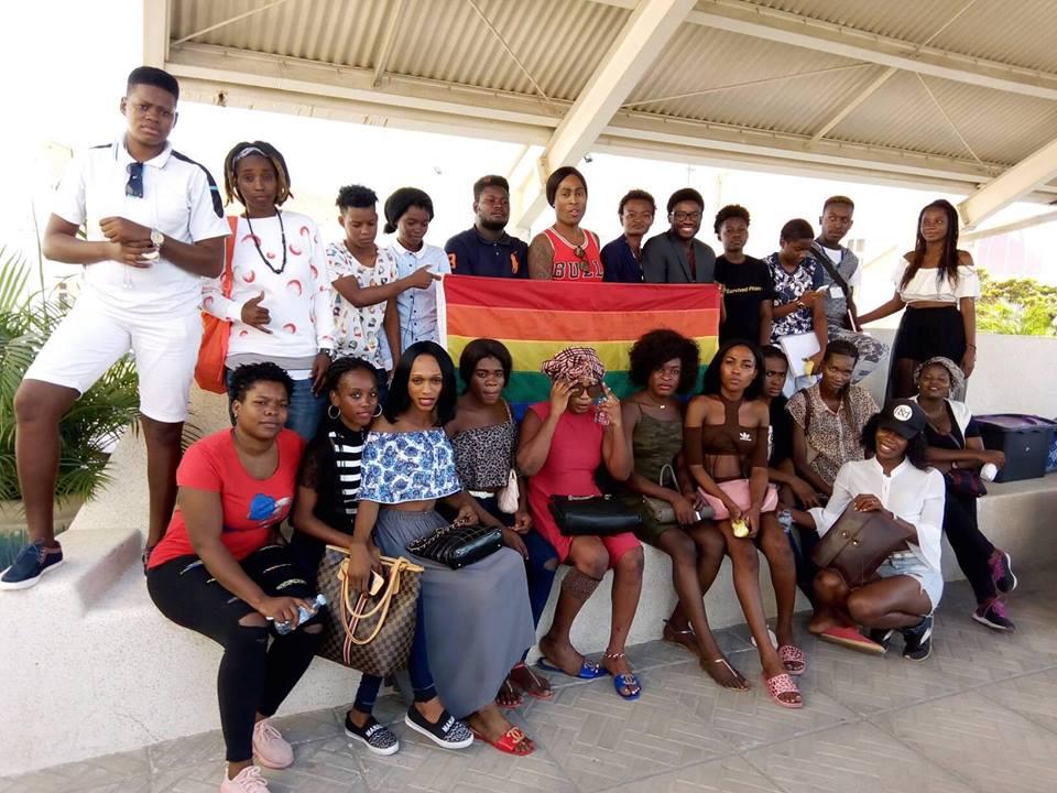 Des membres d'IRIS Angola posent tout au tour d'un drapeau arc-en-ciel.