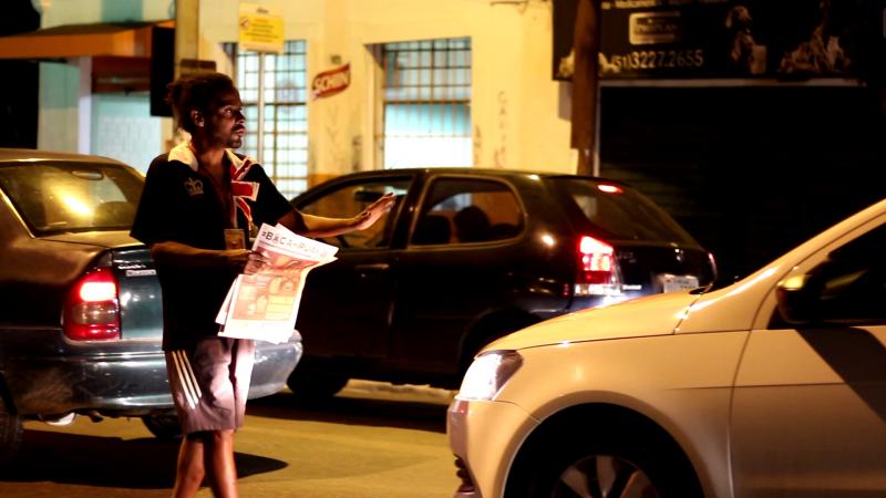 Un homme circule entre les voitures pour vendre le journal Boca de Rua.