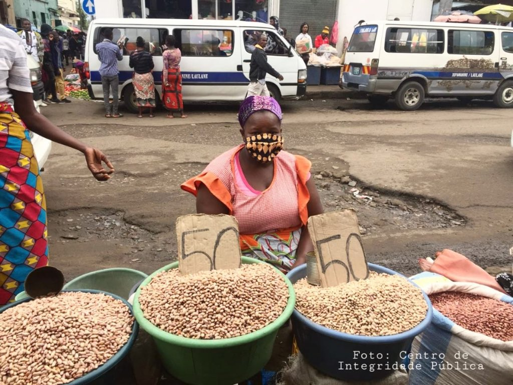 Vendeuse de cacahuètes portant un masque dans une rue passante au Mozambique.