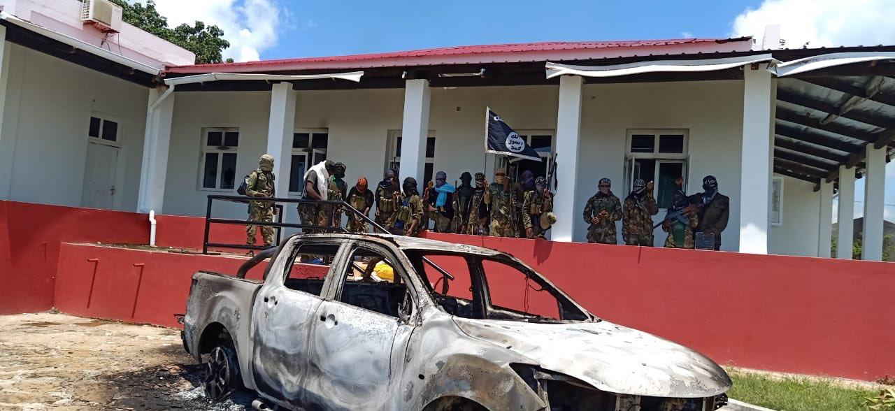 Un groupe de combattants en treillis contemple une voiture calcinée à Cabo Delgado.