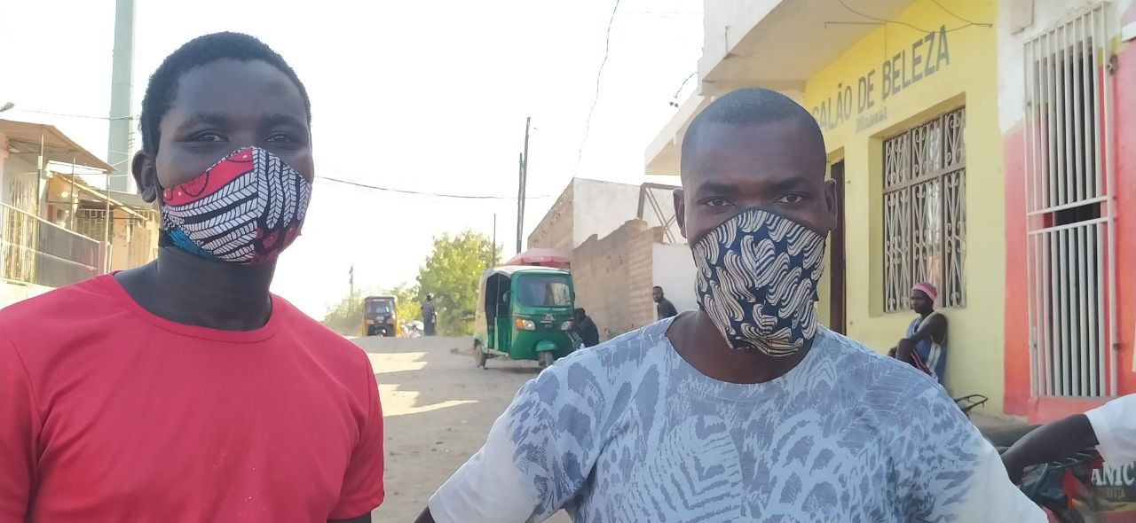 Deux Mozambicains, le visage couvert de masques de fabrication locale