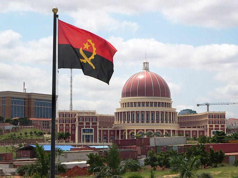 Le Palais de l'Assemblée nationale d'Angola, un bâtiment en demi-cercle au centre duquel se dresse une imposante coupole. Au premier plan flotte le drapeau de l'Angola.