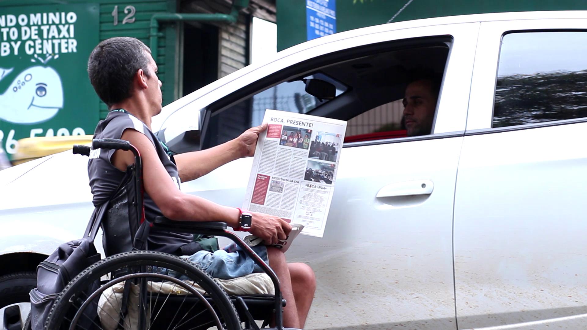 Un homme en fauteuil roulant tend un journal à un automobiliste à Porto Alegre.