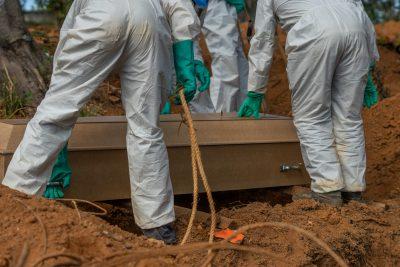 Des employés des pompes funèbres mettent un cercueil en terre, portant un équipement de protection inviduel qui leur couvre le corps tout entier.