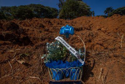 """Un bouquet de fleur agrémenté de rubans bleus et du fanion """"Repose en paix"""" sur une tombe fraichement creusée."""