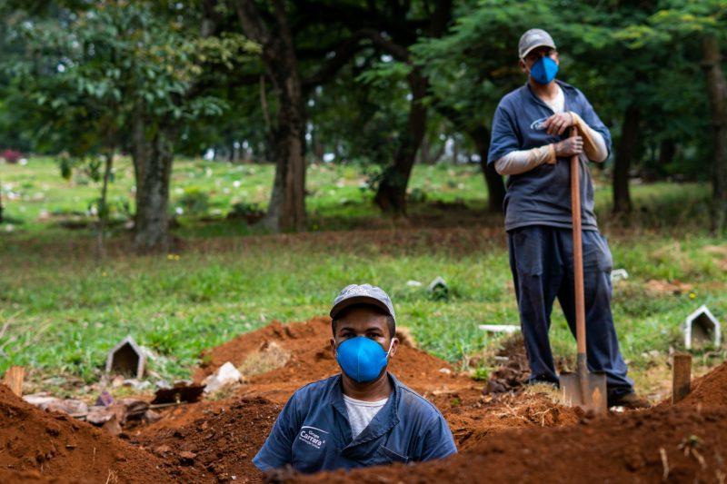 Deux fossoyeurs en uniforme bleu creusent une tombe. Tous deux portent un masque de protection faciale et une casquette.