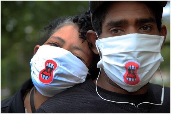 Catarina et Daniel, du journal Boca de Rua, portent des masques de protection faciale avec le logo d'une bouche ouverte.
