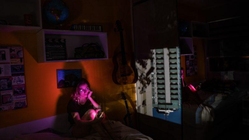 Une étudiante brésilienne dans sa chambre, éclairée par la lumière de son ordinateur portable. Elle se tient assise sur son lit, devant un mur orange.