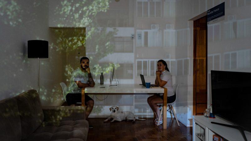 Dans un salon sobrement décoré, un couple est assis face à face à une table, leur chien à leurs pieds. Sur les murs sont projetées des images d'une arbre et d'un grand bâtiment.