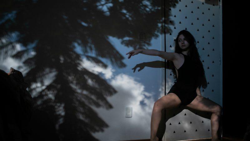 Caroline Muller, en justaucorps, fait des exercices de danse dans son appartement, devant une projection d'un arbre.