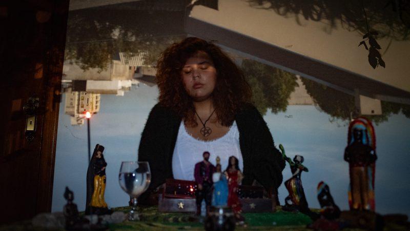 La photographe brésilienne Eveline Medeiros devant son autel, les yeux fermés. Derrière elle, une image inversée d'une vue dégagée du ciel et de quelques bâtiments.
