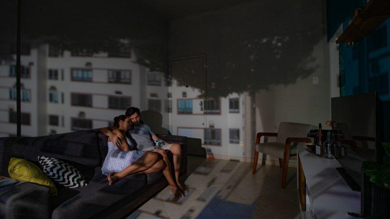 Un couple enlacé sur leur canapé dans un appartement de Rio de Janeiro. Sur les murs, une projection du bâtiment de l'autre côté de la rue.