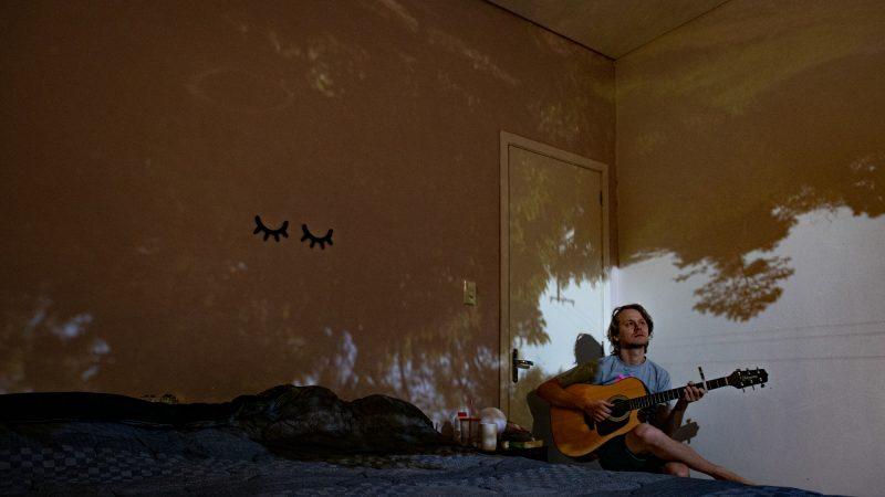 Josué Braun assis seul sur son lit, joue de la guitare. La pièce est sombre et des images d'arbres sont projetées sur les murs.