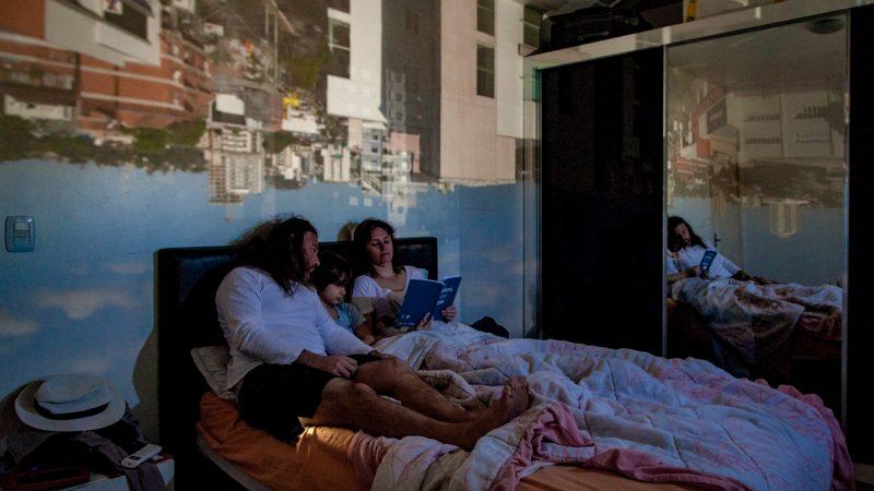 Un couple et leur fils lisent un livre ensemble, assis dans un lit. Au-dessus d'eux, une projection de leur vue extérieure sur plusieurs bâtiments de briques.