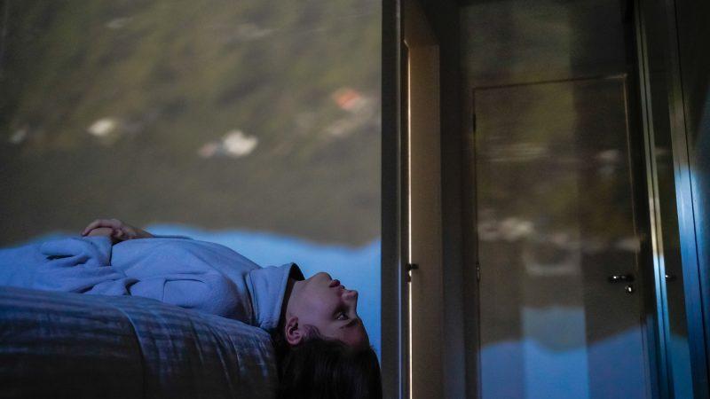 Une adolescente allongée sur son lit, la tête dans le vide. Elle regarde la projection de la rue sur les murs de sa chambre.