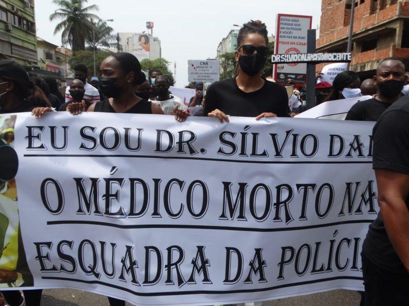 Deux femmes portent une grande bannière lors d'une manifestation contre les violences policières à Luanda.