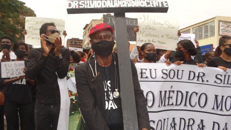A Luanda, une foule de manifestants portent des masques noirs en protestation contre la mort suspecte d'un médecin en garde à vue. Au centre, un homme porte une croix noire.