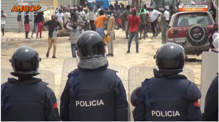 Un cordon de police, de dos, face à une foule clairsemée de manifestants.
