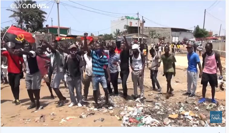 Un groupe de jeunes hommes portant le drapeau angolais marchent à Luanda, le poing levé, pour protester contre le gouvernement.