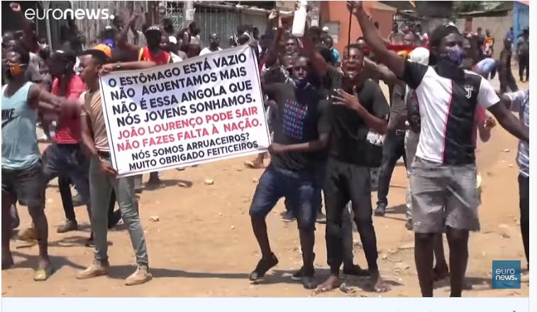 Un groupe de jeunes hommes manifeste à Luanda, tenant une pancarte et levant le point. Ils semblent scander des slogans.