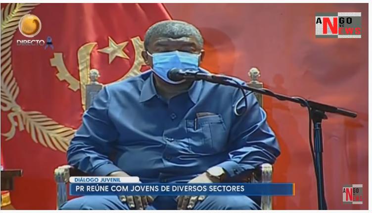 Un homme âgé en costume bleu s'exprime au micro, devant le drapeau de l'Angola. Il porte un masque de protection faciale.