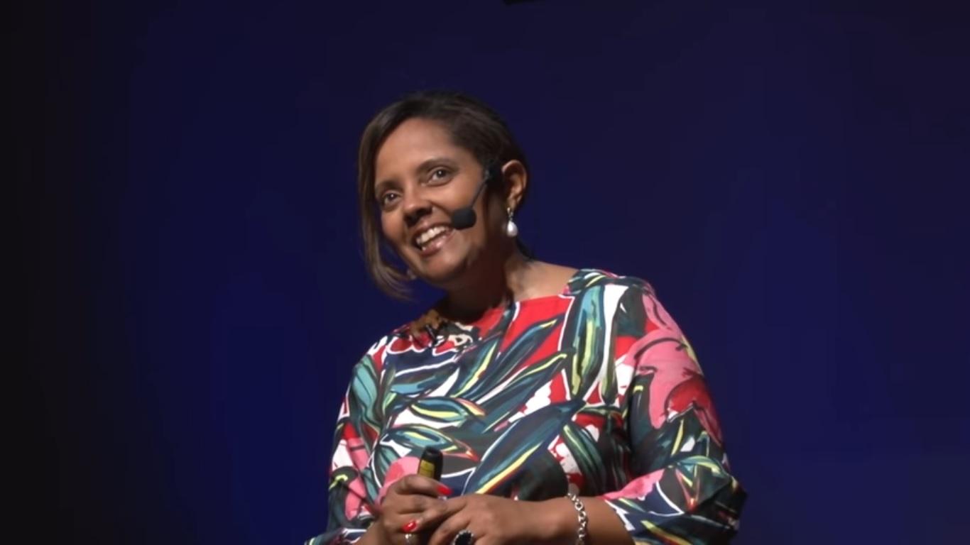 La chercheuse Gladis Kaercher arbore un grand sourire, inclinant la tête. Elle porte un haut aux couleurs chatoyantes.