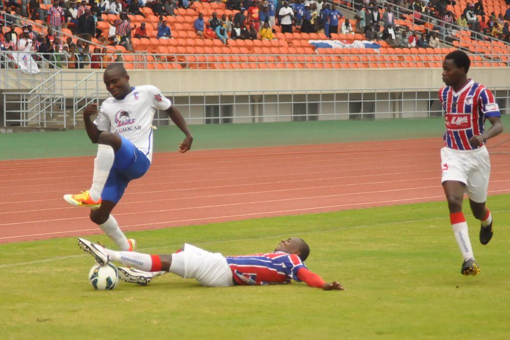 Trois joueurs mozambicains en pleine action sur un terrain de football. L'un est à terre, après un tacle mal négocié.