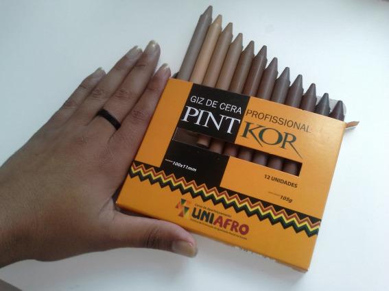 Une boîte de pastels Pintkor avec 12 crayons de différentes teintes de peau tenues par la main d'une femme noire.